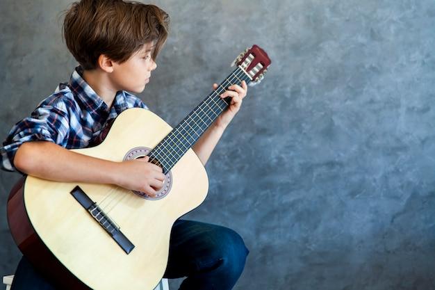 彼のギターを弾く10代の少年