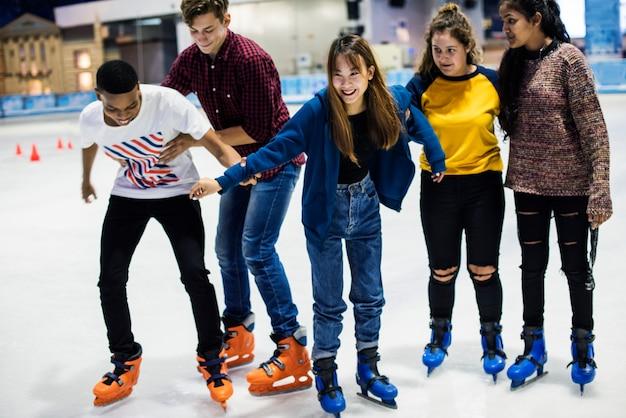 氷のスケートリンクで10代の友人のアイススケートのグループ