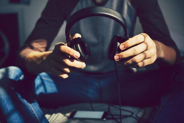 彼のスマートフォンを通して音楽を聞いて寝室で10代の少年