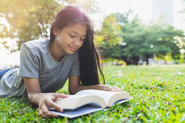 アジアの10代の少女は公園の芝生の上の本を読んで横になっています。