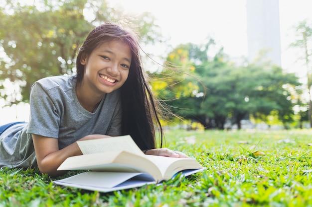 アジアの10代の少女は公園の芝生の上の本を読んだ後笑っています