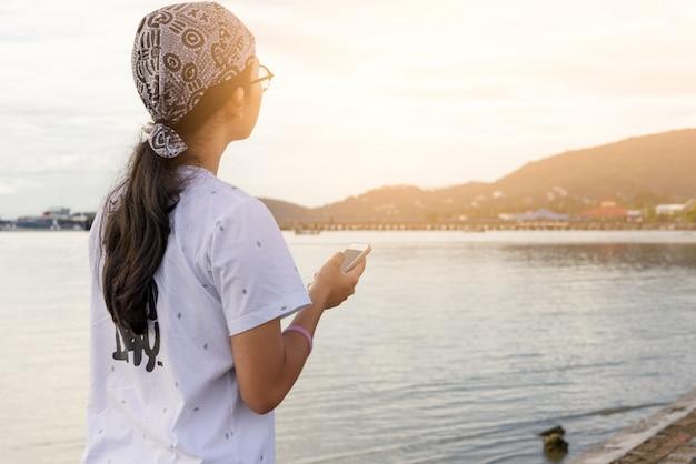 ビーチの夕日で一人で旅行休暇に携帯電話を使用して10代のアジアの女の子
