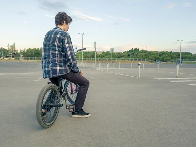 大きなアスファルトスポーツ地面に自転車で身も凍るように座っているカジュアルな10代の少年