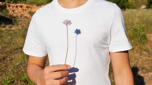 野生の紫色の植物を保持している10代の少年を強い日陰を閉じる