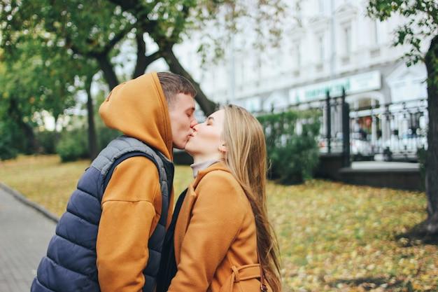 秋の街の通りにキスカジュアルなスタイルに身を包んだ愛10代の若者の友人で幸せな若いカップル