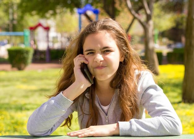 夏の公園で携帯携帯電話のスマートフォンを持つかなり10代の女の子