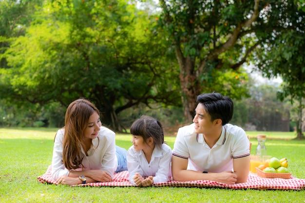 アジアの10代家族の幸せな休日のピクニックの瞬間公園で父と母と娘がマットの上に横になっていると幸せな笑顔で果物と食べ物で緑豊かな庭園で休暇の時間を過ごす。