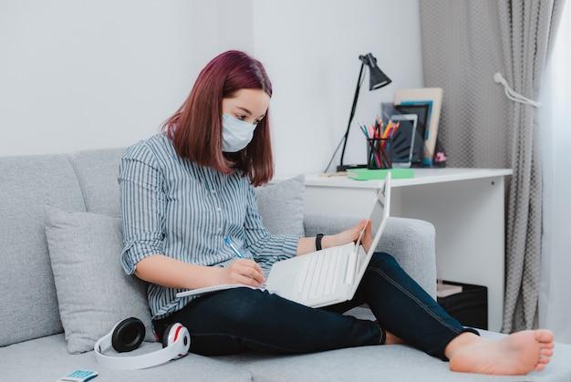 勉強して床リビングルームソファ学生を座っているウイルスに対する医療マスクと10代の女子高生