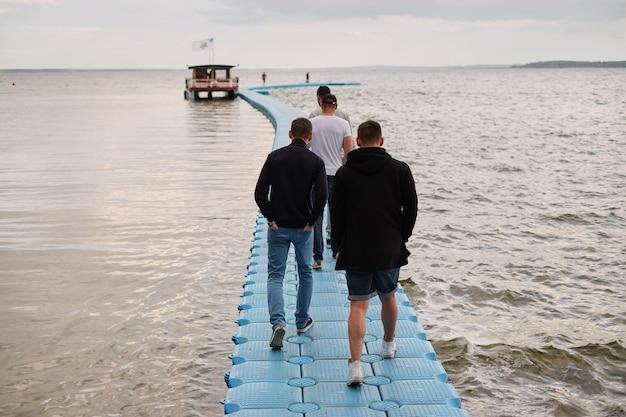 コピースペース、プラスチック製のドックで歩く10代の男性、男性ウォーキングの詳細は桟橋に行く