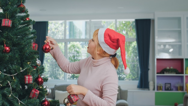 アジアの女性はクリスマスフェスティバルでクリスマスツリーを飾る。幸せな笑みを浮かべて女性10代は、自宅のリビングルームでクリスマス冬の休日を祝います。
