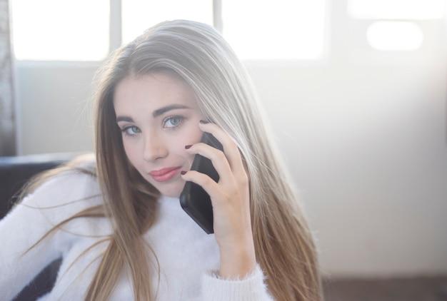 彼女の電話で話している美しい10代の肖像画