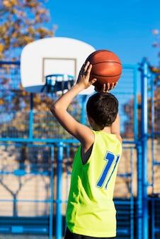 10代のフープにバスケットボールを投げる