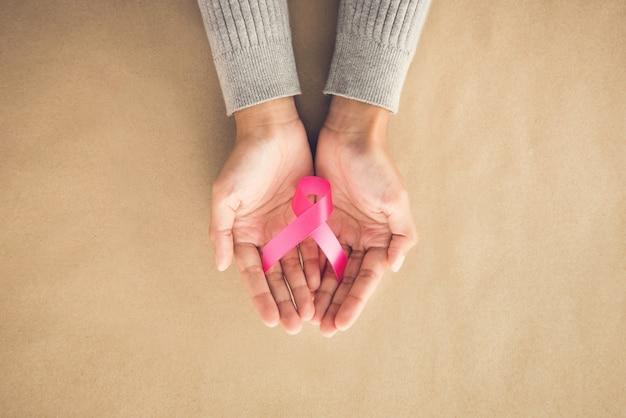 10月の乳がん啓発キャンペーンのシンボルをサポートするサテンのピンクのリボンを与える女性の手