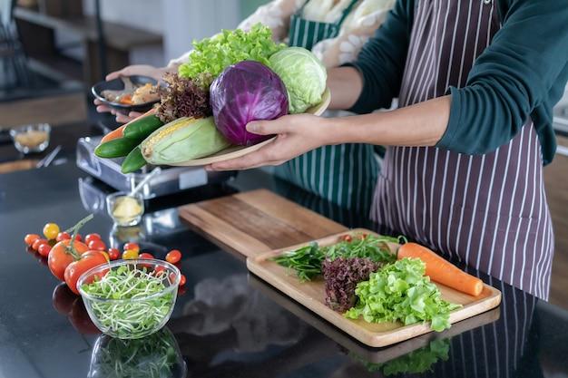キッチンでエビと野菜を示す10代