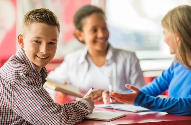 カフェのテーブルに座っている10代の若者のグループ。