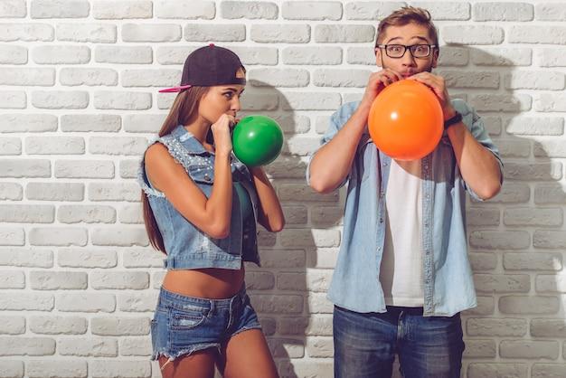 ジーンズの服と帽子で10代のカップルが風船を吹いています。