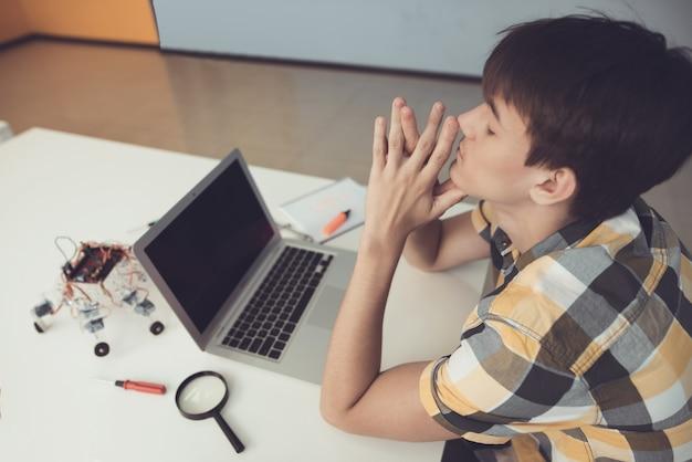 10代の若者がノートパソコンの前のテーブルに座っています。