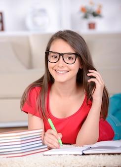 10代の少女が自宅の床に座ってレッスンを教えた