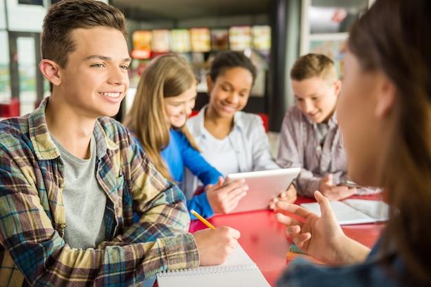 カフェに座って話している10代の若者のグループ。