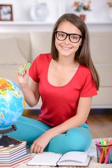 10代の少女の肖像画は床に座ってレッスンを教えた。
