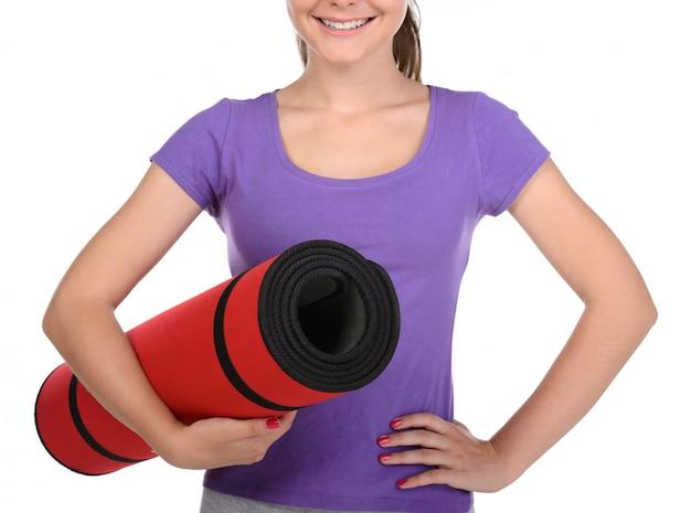 スポーツの10代女性がマットで運動します。