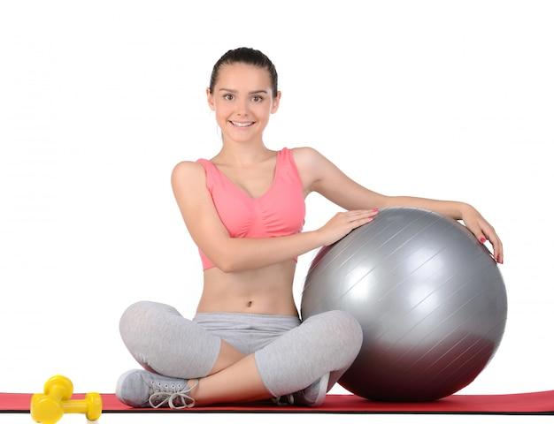 スポーツの10代女性がボールを使って運動します。