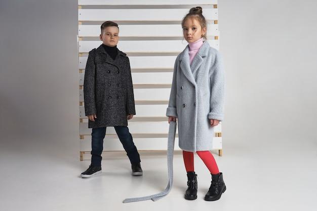 子供と10代の若者のための服の秋コレクション。秋の寒さのためのジャケットとコート。子供たちのポーズ