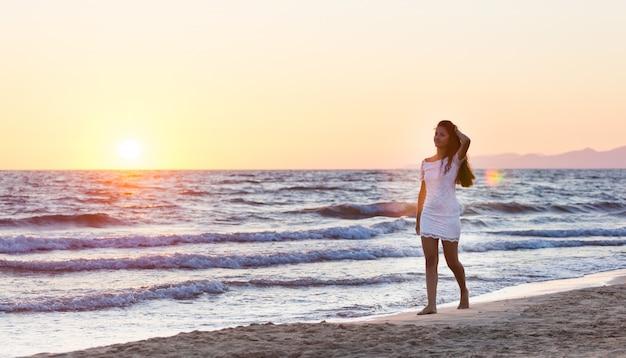 夕暮れ時のビーチの白いドレスと美しい若い10代