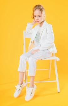 白い服を着た10代の少女が黄色の椅子に座っています。
