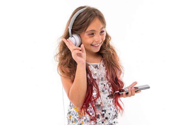 光沢のある明るいドレスで、ピンクで染められた長いブロンドの髪の10代の少女、ヘッドフォンで立って、携帯電話を手に持って
