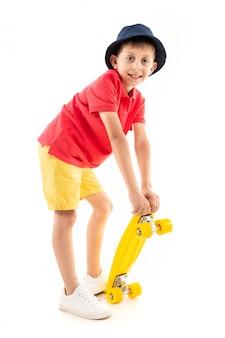 白人の10代の少年が立ち、黄色のペニーを保持しています。