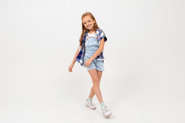 スタイリッシュな服で陽気な10代の女の子が踊り、彼女の人生を楽しむ