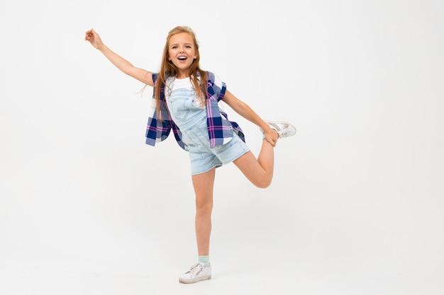 スタイリッシュな服で長い髪の美しい10代の女の子が踊り、彼女の人生を楽しむ