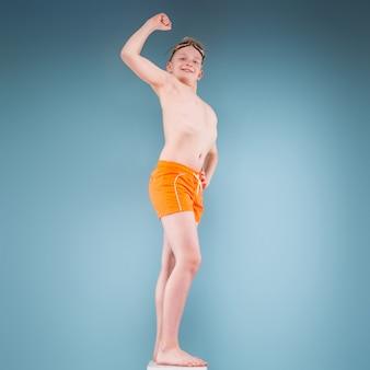 オレンジ色のショートパンツと水泳メガネの10代の少年