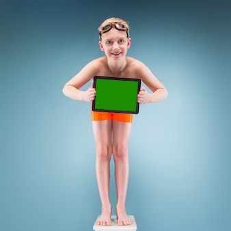 オレンジ色のショートパンツと水泳メガネの10代の少年は空のタブレットを保持します。