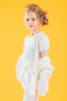 黄色にポーズをとって白い服の10代の少女