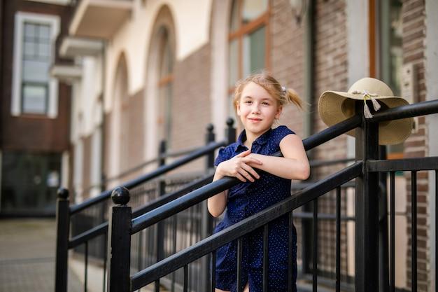 美しい古い家の間で遊んで10歳のブロンドの女の子の肖像画