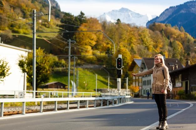 ジェスチャー、交通、旅行、観光、人々-若い女性や10代の少女が街でタクシーをつかんだり、ヒッチハイキング