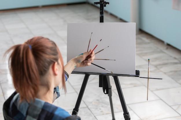 若い10代の女性アーティストは、きれいなキャンバスに油絵の具でペイントするためのさまざまなブラシを保持しています。