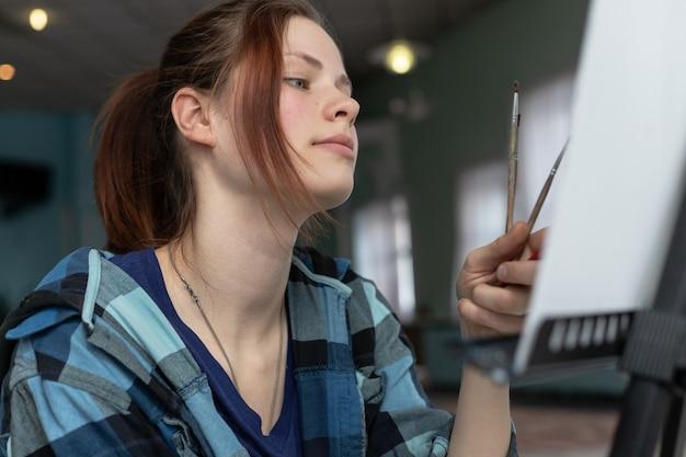 油絵の具で絵を描く過程で若い10代女性アーティスト。