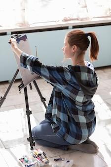 若い10代の女性アーティストは大理石のタイルの床に座っています。油絵の具で描く過程の女性。