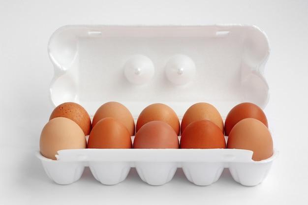 白地に白い発泡スチロールの10の茶色の茶色の卵