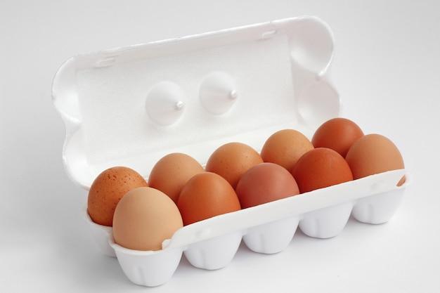 白い発泡スチロールの白い背景の上の10の鶏の茶色の卵。分離しません。