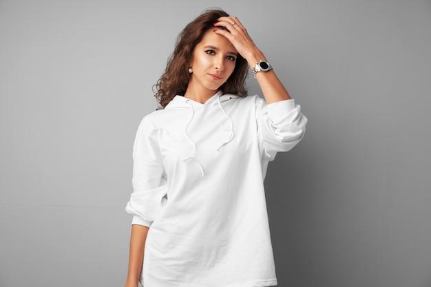 灰色の背景にポーズをとって白いパーカーで美しい女性10代