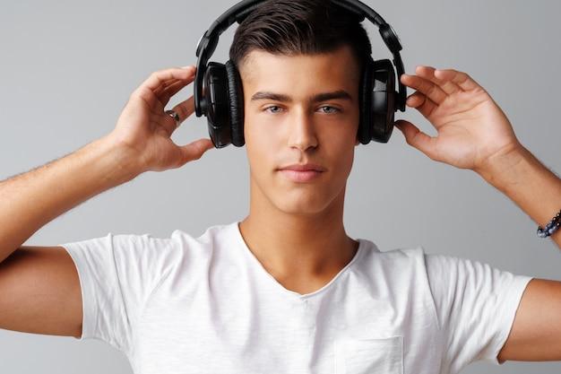 若い男が彼のヘッドフォンで音楽を聴く10代