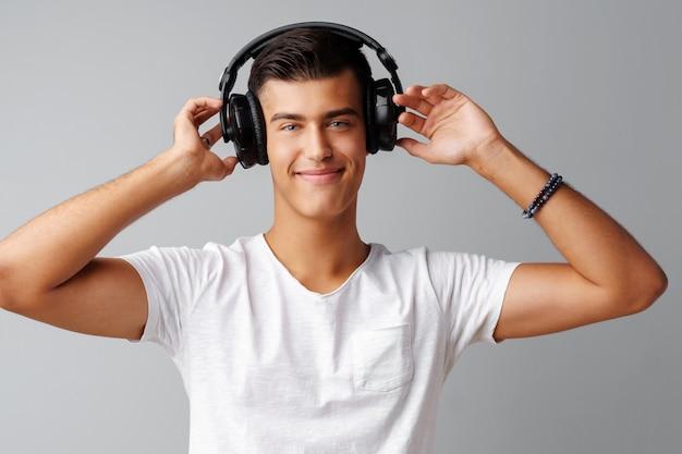 灰色の背景の上の彼のヘッドフォンで音楽を聴く若い男10代