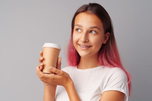 一杯のコーヒーを保持している素敵な10代の女の子