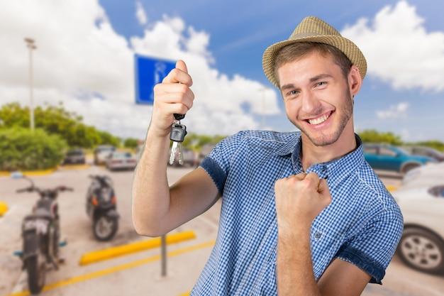 車のキーを保持している魅力的な10代の少年