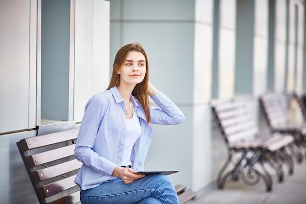 都市に座っているタブレットで若い10代の女の子。