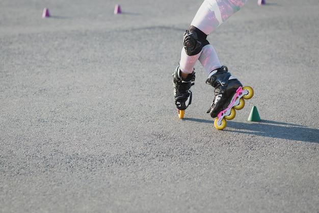 10代のローラーブレードのアスファルトでのトリミングショット、トライアル、ローラーブレードと膝の保護具を着用